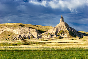 The spire known as Chimney Rock glows warm in the recent sunrise and the surrounding fields are a verdant green from a recent rain. - Nebraska Photograph