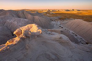 As the sun sets warm sunlight bathes parts of Toadstool Geologic Park in warm hues. - Nebraska Photograph