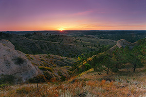 On an early fall morning, the rising sun shines brightly across Chadron State Park, in western Nebraska. - Nebraska Photograph