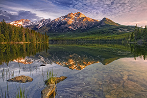 Morning light bathes Pyramid mountain in Jasper National Park.The scene is nearly perfect reflected in the still waters of Pyramid Lake. - Canada Photograph