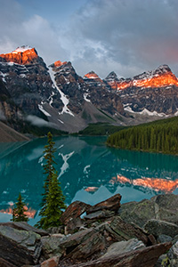One of the most scenic and popular destinations in Banff National Park, Lake Moraine reflects the ten peaks on fire with an early morning glow.  Around 3:30 in the morning I rose to get to Lake Moraine for a 6:00 sunrise.  Since I was 60 miles away, I had to make sure to give myself enough time to get there and get set up.  This scene was my reward. - Canada Photograph