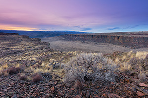 Frechman Coulee in the Columbia River Basin Wildlife Area central Washington is a popular destination for hikers and climbers.  On an unseasonably warm February evening I waited as the sun descended in the distance causing the landscape to be cast in cool purple and blue hues. - Pacific Photograph